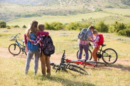 Photo pour Famille de quatre personnes en vélo dans les montagnes - image libre de droit