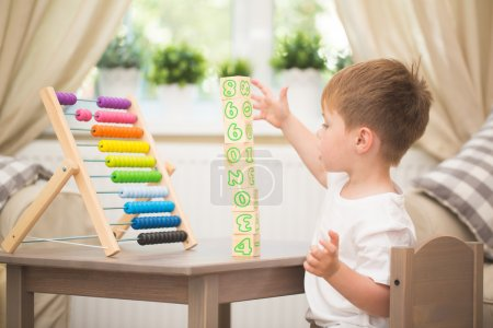 Photo for Little boy playing with abacus toy at home - Royalty Free Image
