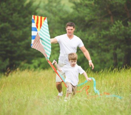 Photo pour Relation père et fils, jouant avec le cerf-volant dans le parc - image libre de droit