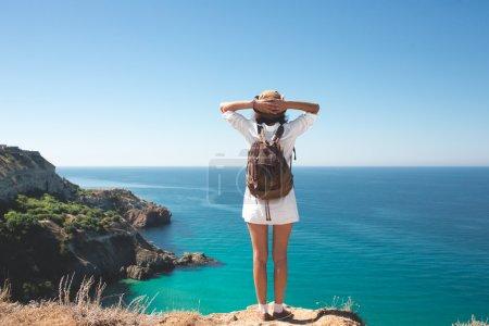 Photo pour Sac à dos voyageur femme debout sur la falaise de la mer  . - image libre de droit
