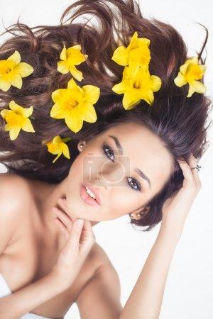 Photo pour Femme avec des fleurs narcis dans les cheveux - image libre de droit