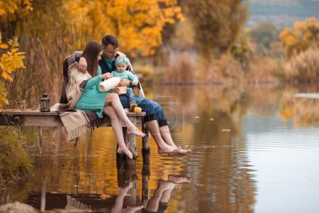 Photo for Young family resting on the lake shore - Royalty Free Image