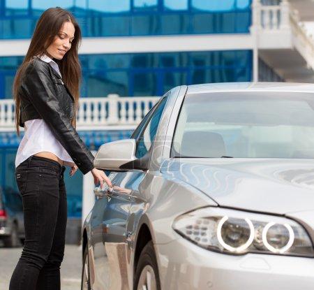 Photo pour Portrait de belle jeune femme près de la nouvelle voiture - en plein air - image libre de droit