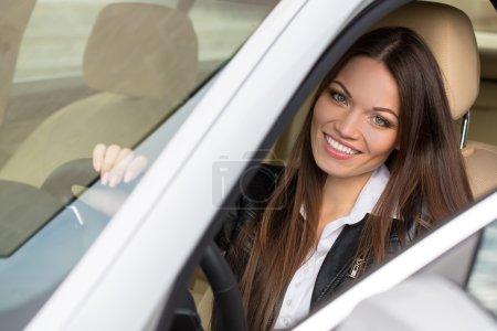 Photo pour Portrait de belle jeune femme dans la nouvelle voiture - en plein air - image libre de droit