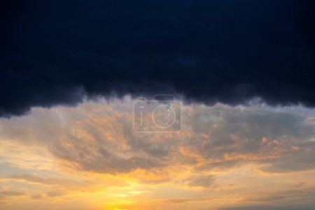 Photo pour Énorme pluie nuage éclairé coucher de soleil orange - image libre de droit