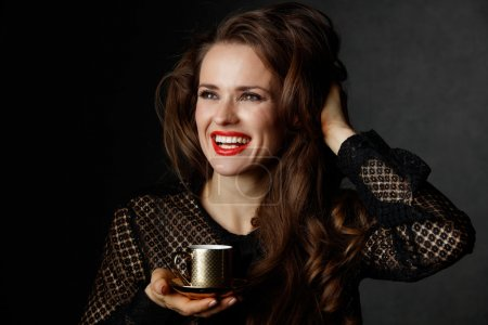 Smiling with brown hair holding cup of coffee on dark background