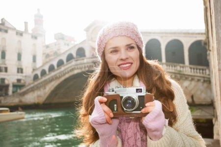 Happy woman tourist with retro photo camera near Rialto Bridge
