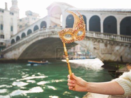 Photo pour Escapade ultime raccourci - début du Nouvel An en cours sur Carnaval à Venise, Italie. Gros plan sur la main d'une femme tenant le masque de Venise devant le pont du Rialto - image libre de droit