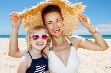 Photo for Family fun on white sand. Portrait of smiling mother and daughter under big straw hat at sandy beach on a sunny day - Royalty Free Image