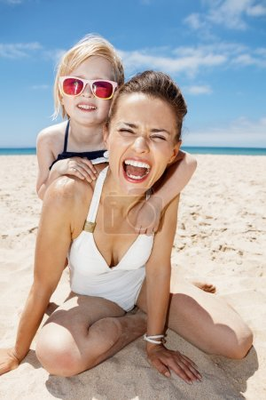 Photo for Family fun on white sand. Portrait of smiling mother and daughter in swimsuits at sandy beach on a sunny day - Royalty Free Image