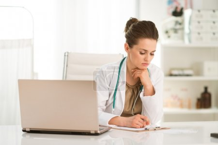 Thoughtful female doctor sitting at a desk in the office