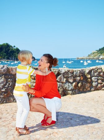 Happy mother and daughter hugging in front of lagoon with yachts