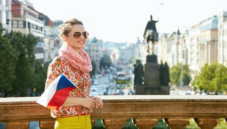 Woman with Czech flag standing near National Museum in Prague
