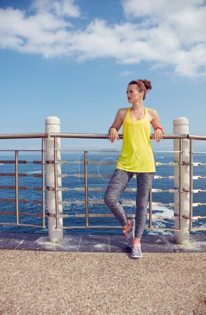 Relaxed fitness woman looking into distance at embankment