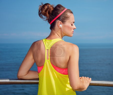 Relaxed fitness woman listening to music at embankment