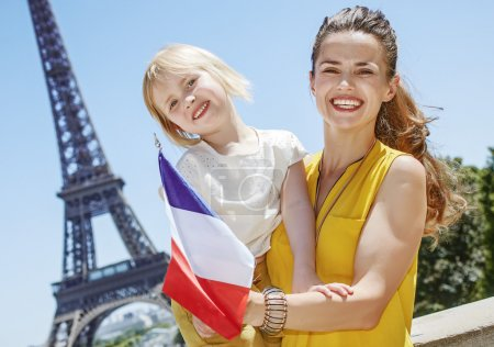 Photo for Having fun time near the world famous landmark in Paris. happy mother and daughter showing flag in the front of Eiffel tower - Royalty Free Image