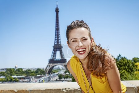 Photo for Having fun time near the world famous landmark in Paris. Portrait of smiling young woman in bright blouse against Eiffel tower - Royalty Free Image