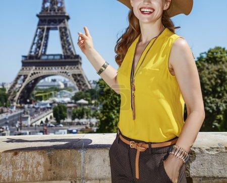 Photo pour Amusez-vous bien près du monument mondialement connu de Paris. Gros plan sur la jeune femme heureuse en chemisier lumineux pointant sur la tour Eiffel contre la tour Eiffel - image libre de droit