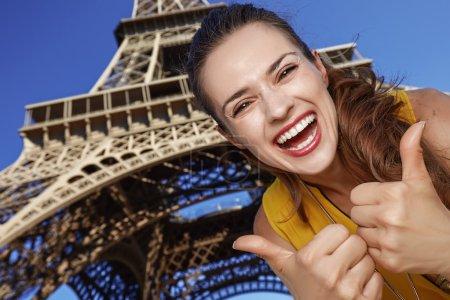 Photo pour Touriste, sans aucun doute, mais si amusant. jeune femme souriante montrant les pouces devant la tour Eiffel à Paris, France - image libre de droit