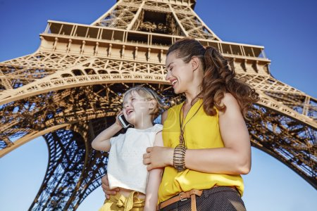 Photo pour Touriste, sans aucun doute, mais si amusant. heureux touristes mère et fille utilisant un téléphone portable à l'avant de la tour Eiffel à Paris, France - image libre de droit