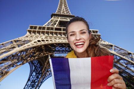 Photo pour Touriste, sans aucun doute, mais si amusant. Portrait d'une jeune femme souriante arborant un drapeau contre la tour Eiffel à Paris, France - image libre de droit