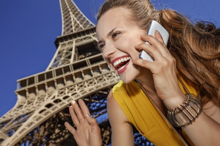 Photo for Touristy, without doubt, but yet so fun. smiling young woman speaking on a cell phone and hand waving against Eiffel tower in Paris, France - Royalty Free Image