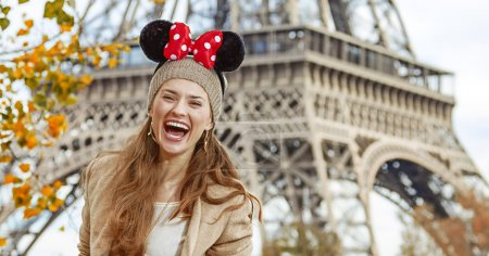 tourist woman wearing Minnie Mouse Ears on embankment in Paris