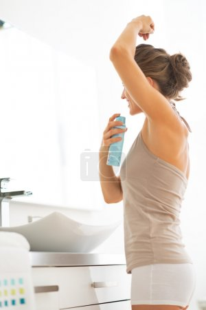 Young woman applying deodorant on underarm