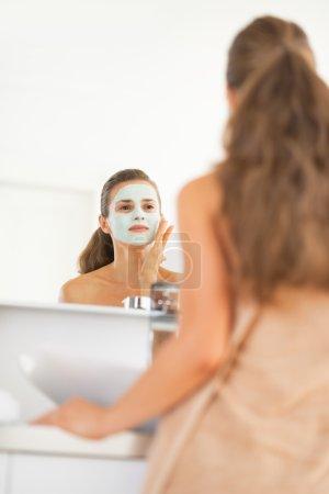 Young woman wearing facial cosmetic mask