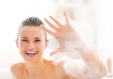 Portrait of happy young woman in bathtub showing foam