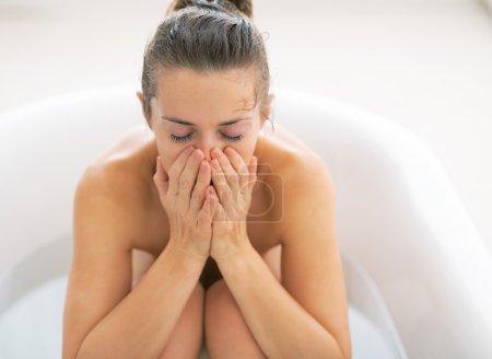 Stressed young woman sitting in bathtub