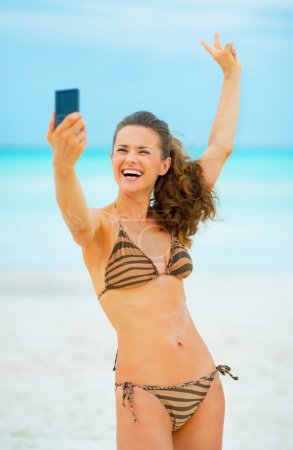 Cheerful young woman taking self photo on beach