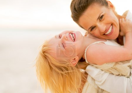 Smiling mother and baby girl having fun time on the beach in the