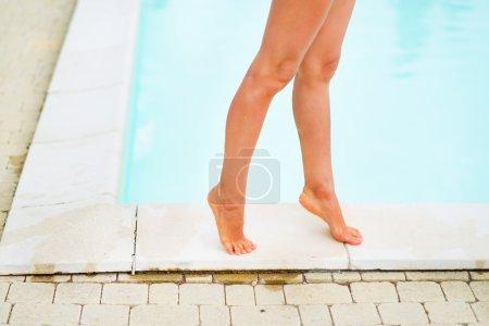 Closeup on young woman legs near swimming pool