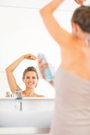 Happy young woman applying deodorant on underarm in bathroom