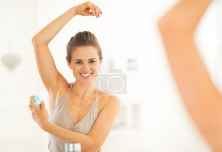 Photo for Happy young woman applying deodorant on underarm - Royalty Free Image