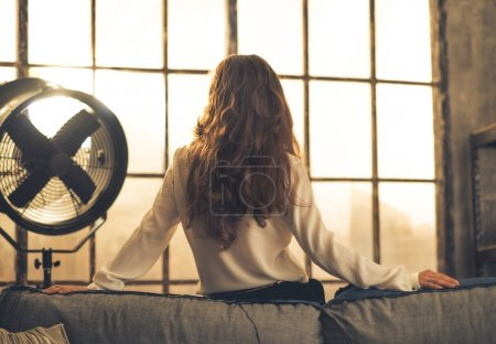Photo for Young woman looking in window in loft apartment. rear view - Royalty Free Image