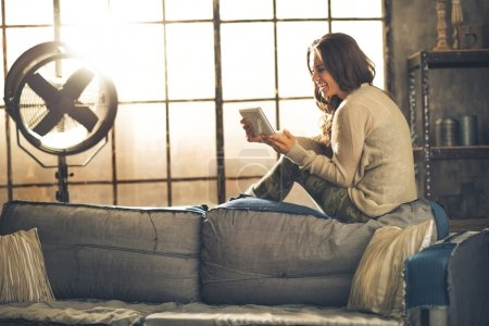 Happy young woman sitting in loft apartment and using tablet pc