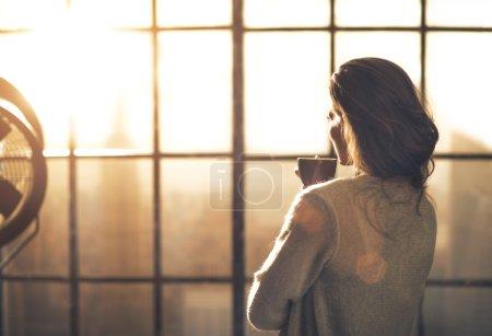 Photo pour Jeune femme dégustant une tasse de café dans un appartement loft. vue arrière - image libre de droit