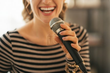 Closeup on young woman singing with microphone in loft apartment