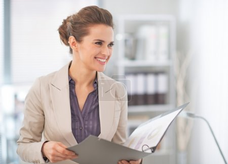 Happy business woman with documents in office