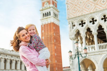 Portrait of happy mother and baby against campanile di san marco