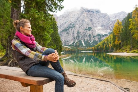 Young woman sitting while on lake braies in south tyrol, italy a