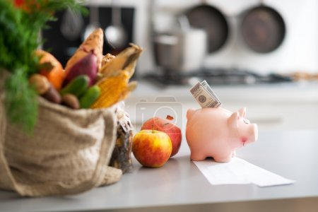 Photo for Closeup on money in piggy bank and purchases from local market on table - Royalty Free Image
