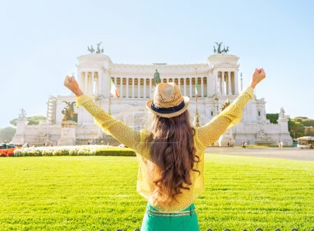 Young woman on piazza venezia in rome, italy rejoicing. rear vie