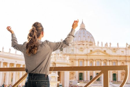 Young woman rejoicing in front of basilica di san pietro in vati