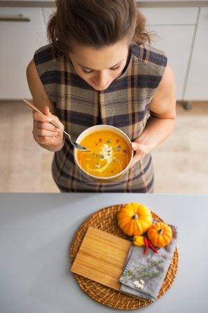 Closeup on young housewife eating pumpkin soup