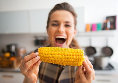 Closeup on young woman eating boiled corn