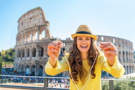 Photo pour Joyeux jeune femme donnant écouteurs avec guide audio devant le colosseum à Rome, Italie - image libre de droit
