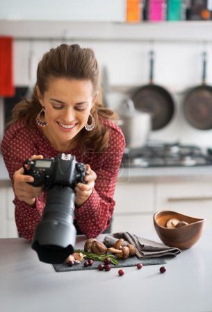 Photo for Happy female food photographer checking photos in camera - Royalty Free Image